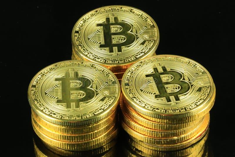 Pila di cryptocurrency di Bitcoins su un fondo nero immagini stock