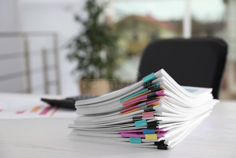 Pila di documenti con le graffette sulla tavola dell'ufficio immagini stock libere da diritti
