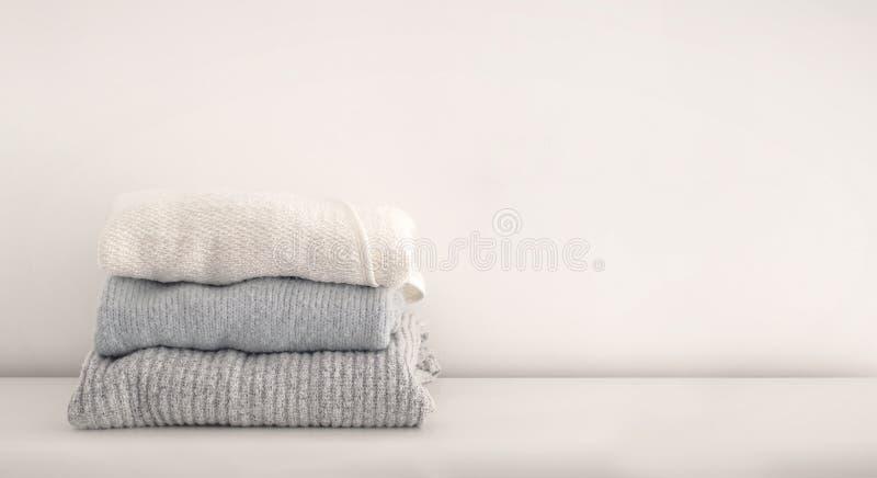 Pila di lavori o indumenti a maglia di lana ordinatamente piegati Stile di vita minimo, capsu fotografie stock