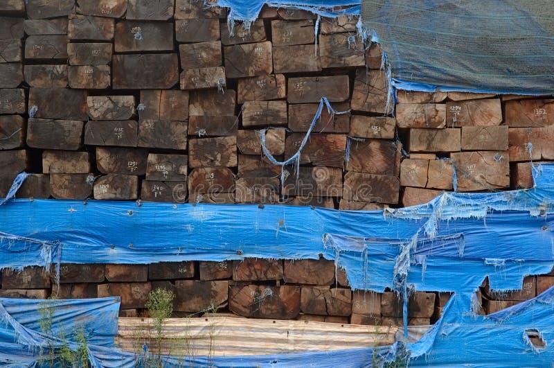 Pila di legami trasversali della ferrovia di legno stagionata coperti da plastica lacerata blu fotografie stock libere da diritti