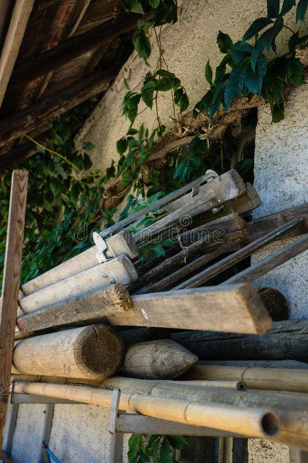 Pila di legno e di strumenti per il giardinaggio accatastato su accanto ad una parete immagini stock