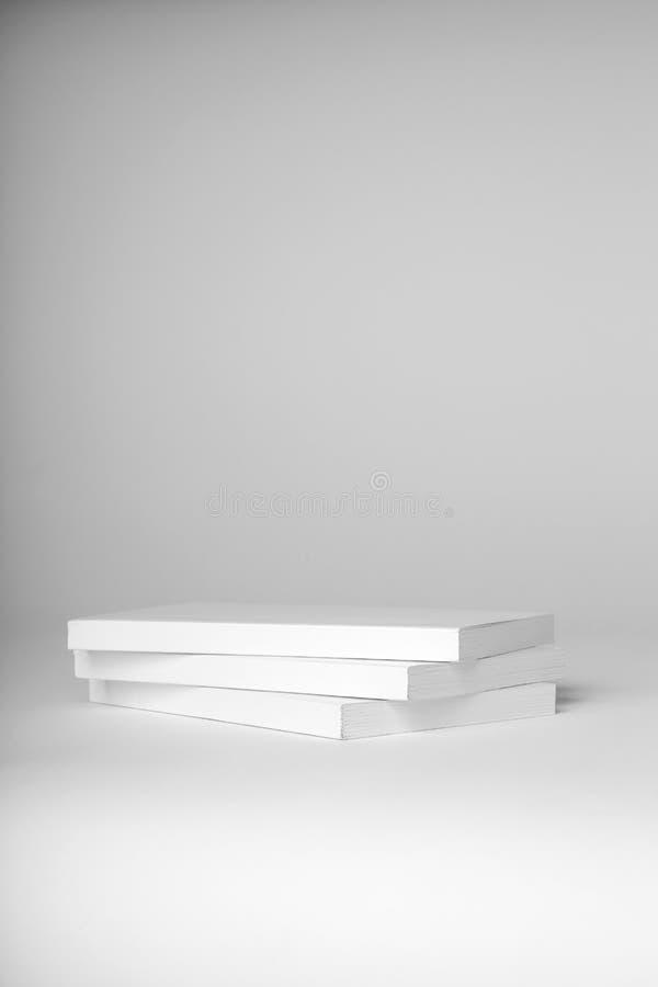 Pila di libri bianchi del libro in brossura reale su un fondo grigio fotografia stock libera da diritti