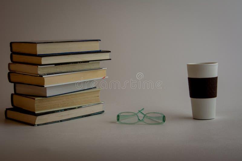 Pila di libri con i vetri e la tazza di caffè immagini stock