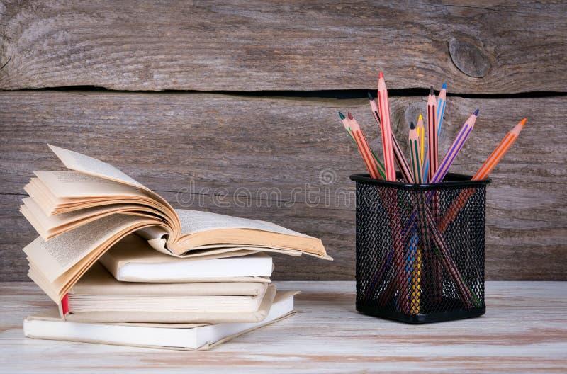 Pila di libri e di matite sulla tavola di legno fotografia stock libera da diritti