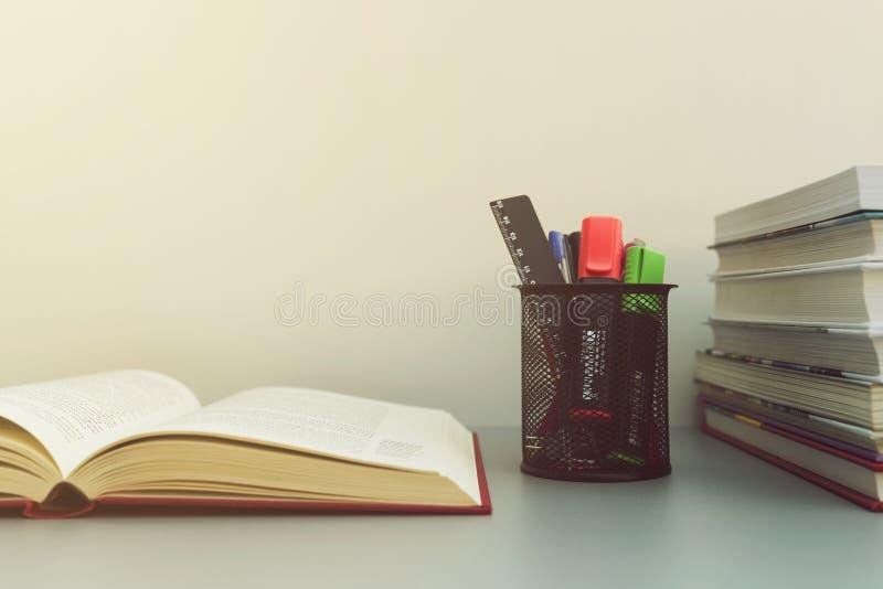Pila di libri, di libro aperto e di strumenti della scuola sulla tavola back fotografia stock libera da diritti