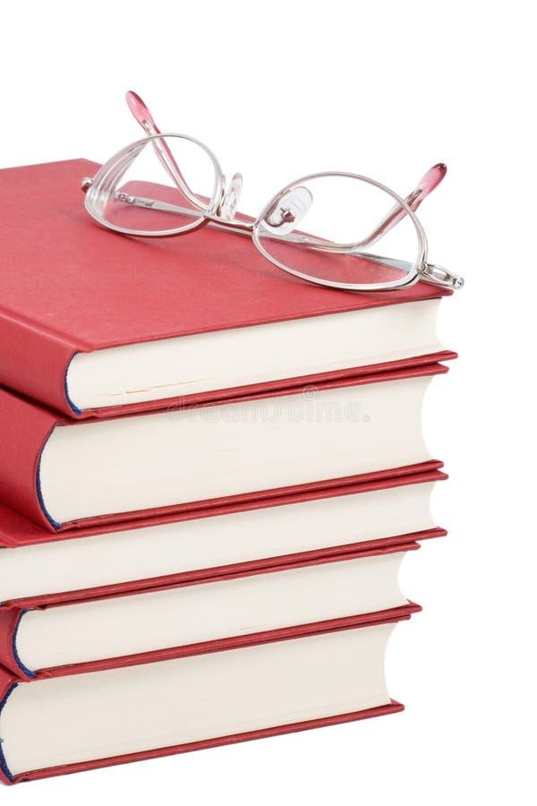 Pila di libri rossi con gli occhiali immagini stock libere da diritti
