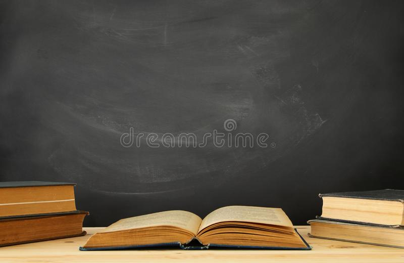 pila di libri sopra lo scrittorio di legno davanti alla lavagna immagini stock