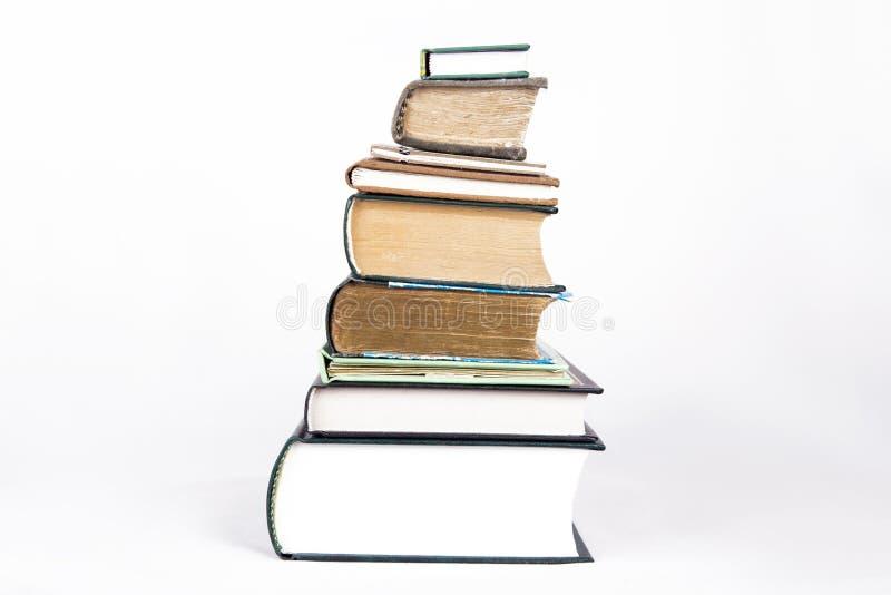 Pila di libri su una priorità bassa bianca fotografia stock
