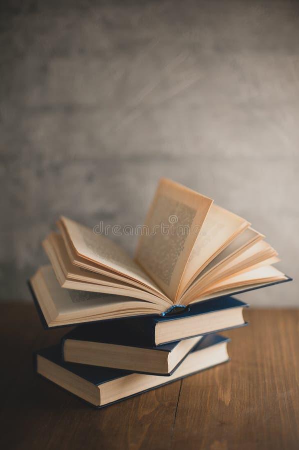Pila di libri su una tavola di legno e sul backg grigio del muro di cemento immagine stock libera da diritti
