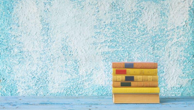 Pila di libri sulla parete blu fotografie stock libere da diritti