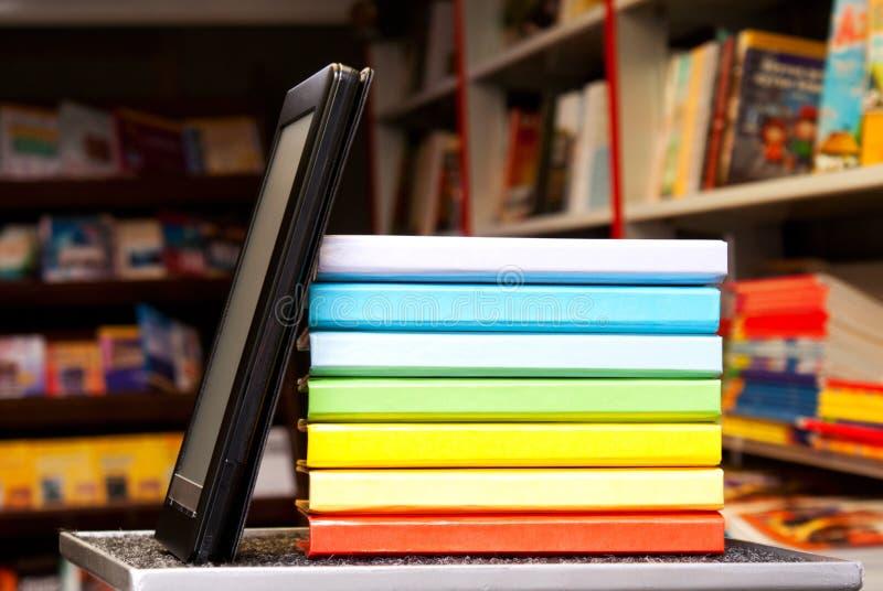 Pila di libri variopinti con il lettore del e-libro fotografia stock libera da diritti