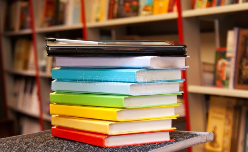 Pila di libri variopinti con il lettore del e-libro immagini stock libere da diritti