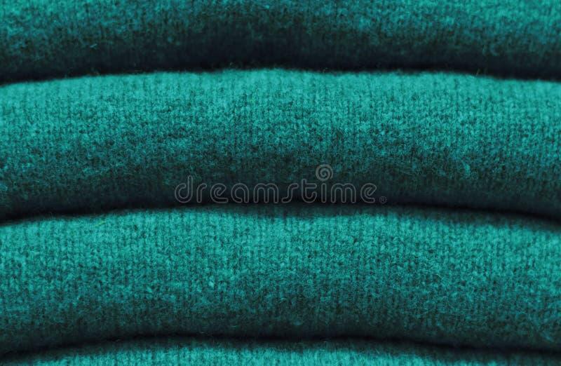 Pila di maglioni di lana primo piano, struttura, fondo di verde del quetzal di tendenza fotografia stock libera da diritti