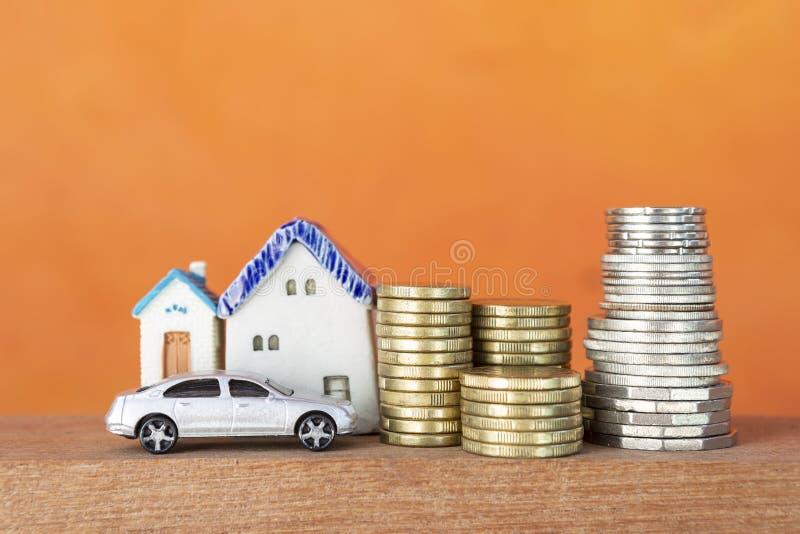 Pila di moneta d'argento e dorata con la casa miniatura e di automobile sopra fondo arancio vago immagini stock libere da diritti