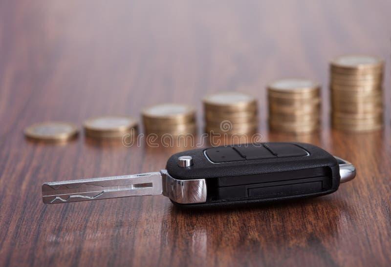 Pila di monete con la chiave dell'automobile immagine stock