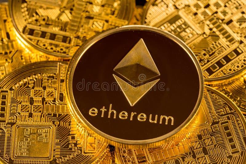 Pila di monete dell'etere con il fondo dell'oro immagini stock libere da diritti