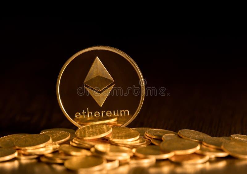 Pila di monete dell'etere con il fondo dell'oro immagine stock