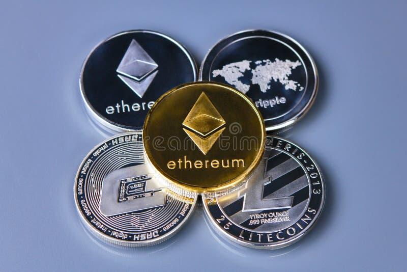 Pila di monete o di ethereum dell'etere sul fondo dell'oro immagini stock