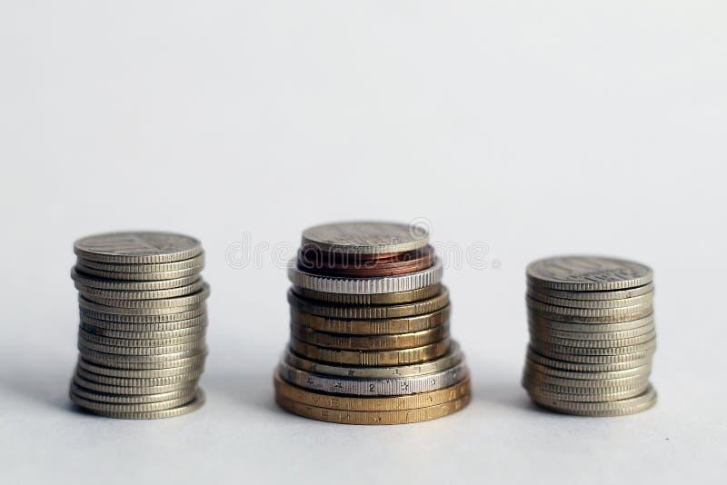 Pila di monete su priorità bassa bianca fotografia stock libera da diritti