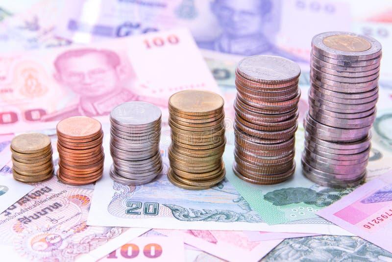 Pila di monete tailandesi sul fondo dei soldi delle banconote fotografia stock libera da diritti