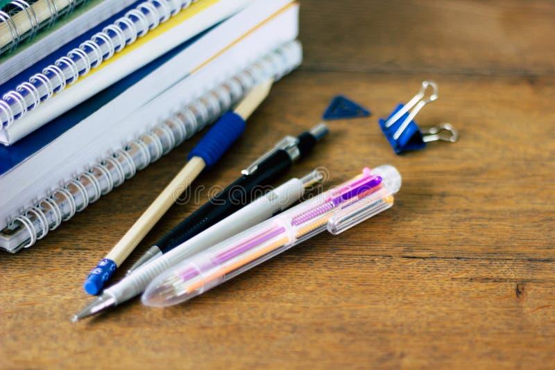 Pila di notebads e di penne sulla tavola di legno fotografia stock libera da diritti