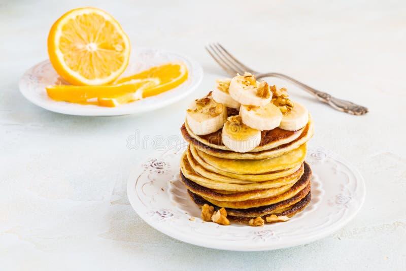 Pila di pancake casalinghi con la banana, lo sciroppo d'acero e le noci sul piatto d'annata immagini stock libere da diritti