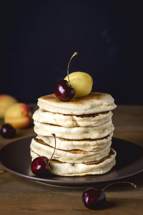 Pila di pancake casalinghi saporiti con il pancake americano saporito della foto scura verticale di frutta fresca tonificato fotografia stock libera da diritti