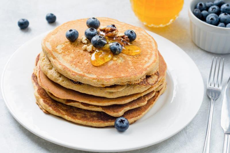 Pila di pancake con i mirtilli, le noci ed il miele sul piatto bianco immagine stock