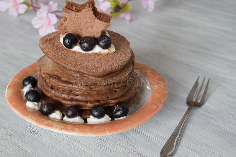 Pila di pancake del cioccolato con le guarnizioni dei mirtilli fotografia stock