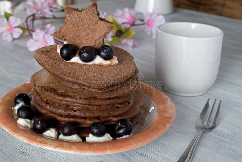 Pila di pancake del cioccolato con le guarnizioni dei mirtilli immagine stock libera da diritti
