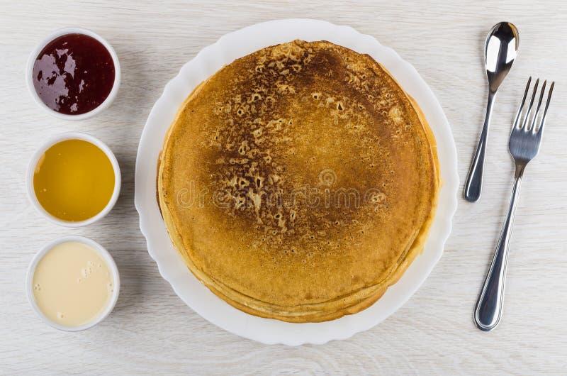 Pila di pancake russi indish, inceppamento di fragola, miele, condens immagini stock libere da diritti