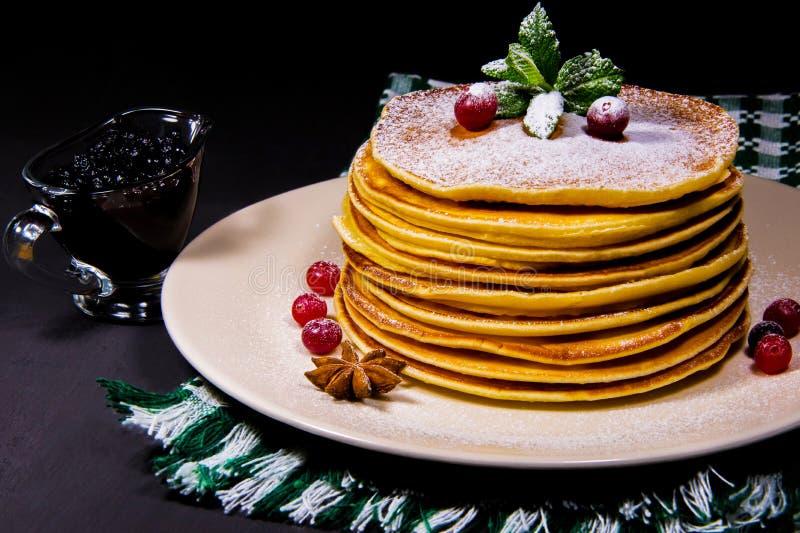 Pila di pancake su un piatto bianco con i budini verdi e la cannella del mirtillo rosso della strofinata spruzzati con la polvere fotografia stock