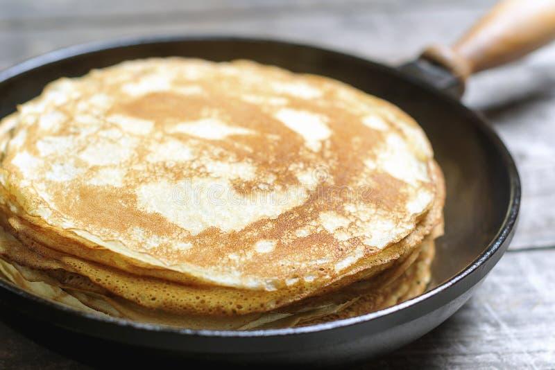 Pila di pancake su una padella della ghisa rustic immagine stock