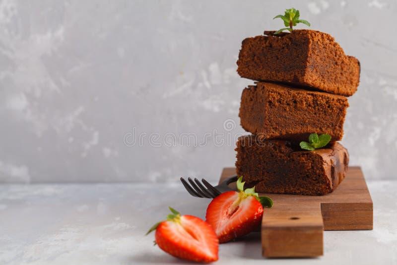 Pila di pezzi di brownie casalingo del cioccolato fondente con strawber immagini stock libere da diritti