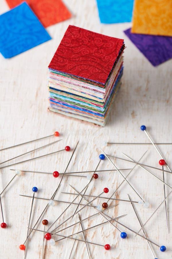 Pila di pezzi quadrati di tessuti variopinti e di mucchio dei perni di cucito della testa multicolore della palla fotografia stock