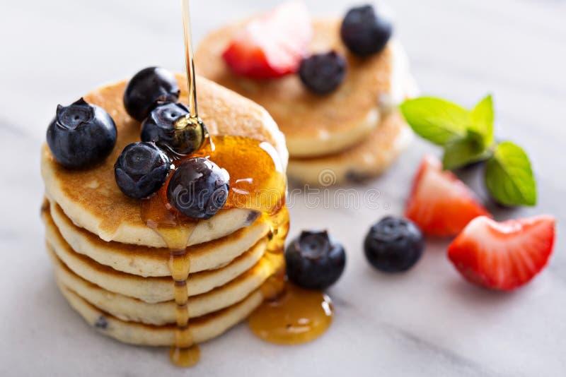 Pila di piccoli pancake con le bacche fotografia stock libera da diritti