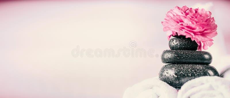 Pila di pietre di massaggio della stazione termale con i fiori e gli asciugamani rosa, fondo di benessere fotografia stock libera da diritti