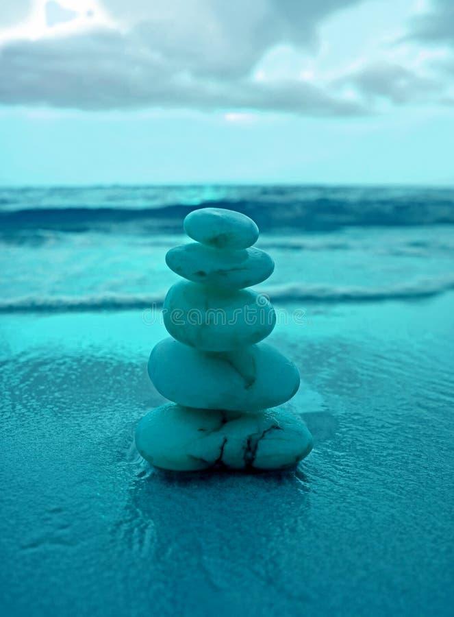 Pila di pietre equilibrate del ciottolo sulla spiaggia contro la spruzzatura delle onde nel colore blu immagini stock