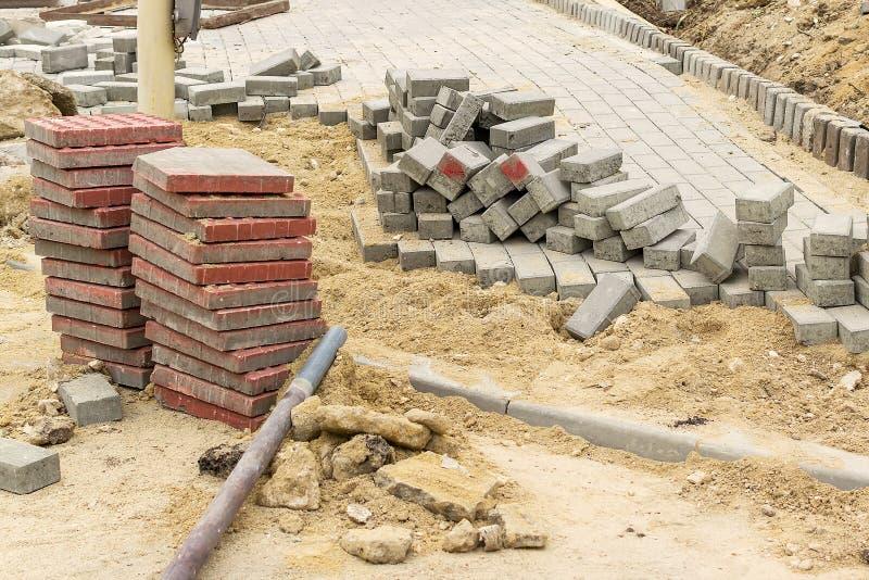 Pila di pietre rosse della pavimentazione al sito dei lavori stradali Costruzione e riparazione del marciapiede Miglioramento del fotografie stock libere da diritti