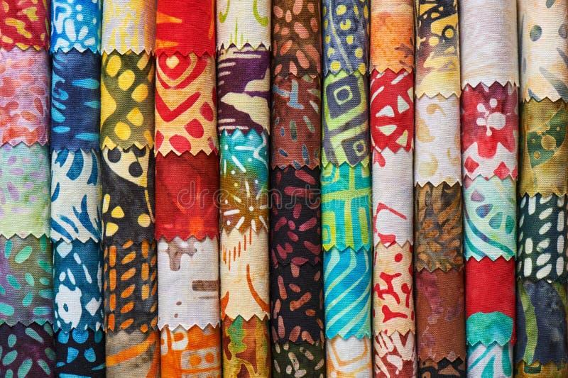 Pila di tessuti imbottenti variopinti del batik come immagine di sfondo vibrante immagine stock