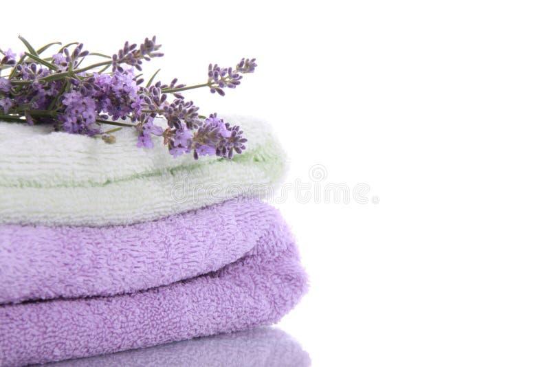 Pila di tovaglioli di Terry con i fiori della lavanda fotografie stock libere da diritti