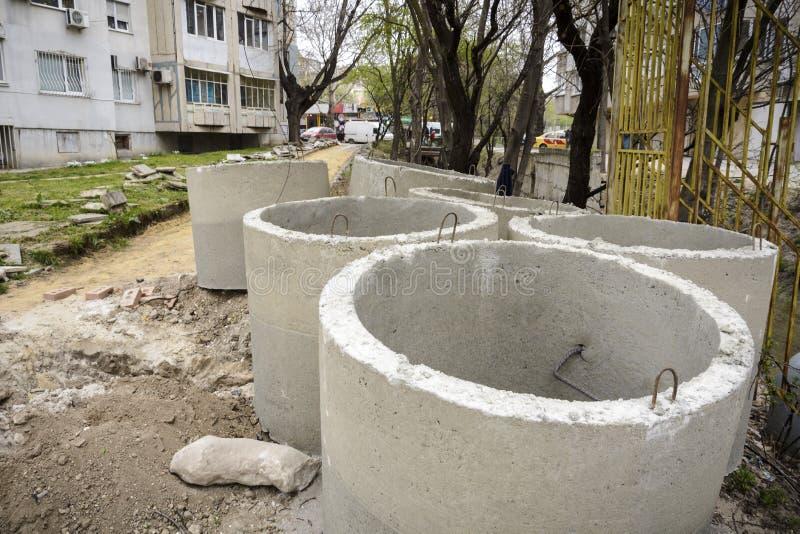 Pila di tubi concreti della fogna in un cantiere fotografia stock