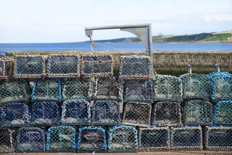 Pila di vasi della rete dell'aragosta al porto dalla parete di pietra affinchè pescatore prendano pesce di mare ed alimento fotografia stock