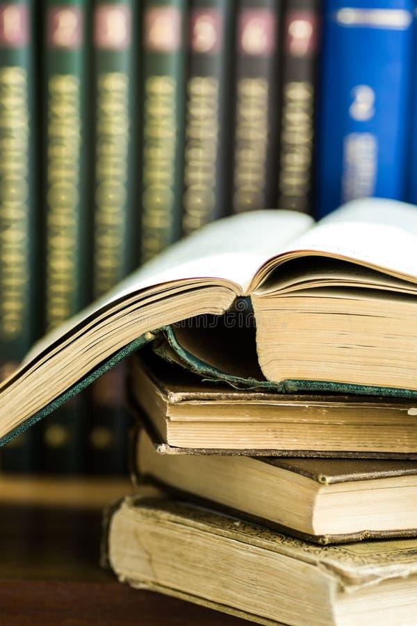 Pila di vecchi libri aperti usati, volumi con la copertura impressionata nei precedenti, istruzione dell'università, leggente con fotografia stock