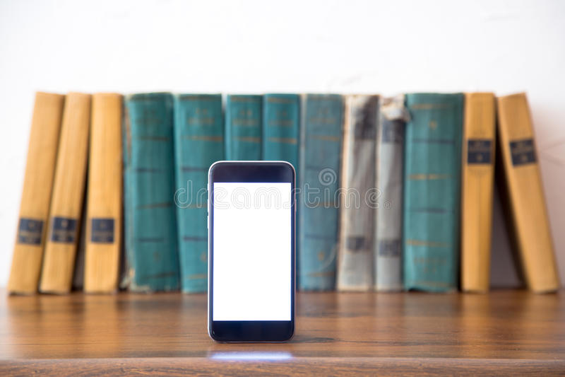 Pila di vecchi libri e di smartphone sopra la tavola di legno, retro immagine filtrata fotografie stock libere da diritti