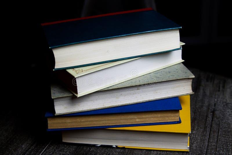 Pila di vecchi libri sulla tavola di legno rotonda con la lettura della luce durante la notte immagine stock