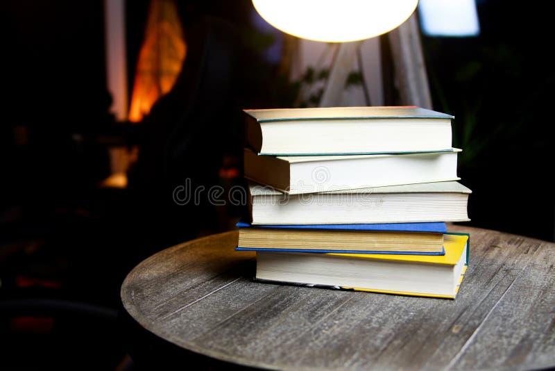 Pila di vecchi libri sulla tavola di legno rotonda con la lettura della luce durante la notte fotografia stock libera da diritti