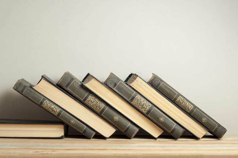 Pila di vecchi libri sullo scrittorio di legno Copi lo spazio per testo Di nuovo al banco Fondo di istruzione immagini stock