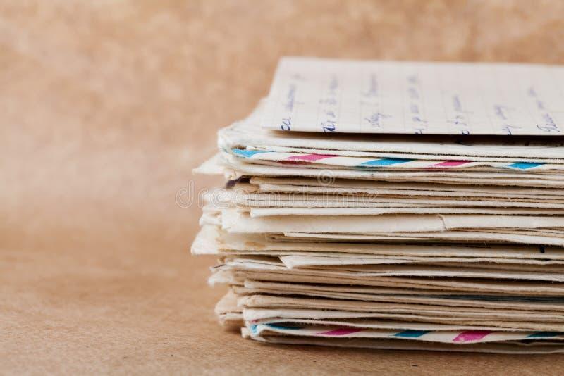 Pila di vecchie buste e lettere sulla carta kraft immagine stock