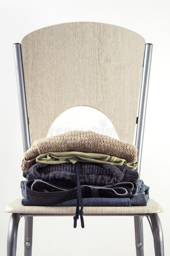 Pila di vestiti su una sedia di legno fotografia stock libera da diritti